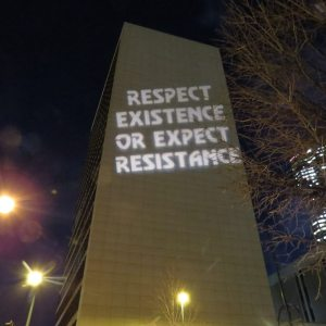 """Side of Denver, Colorado Federal Building with projected sign reading """"RESPECT EXISTENCE OR EXPECT RESISTANCE"""""""