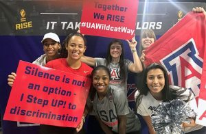 Group of six women University of Arizona Wildcats athletes holding signs for RISE (Ross Initiative in Sports for Equality)