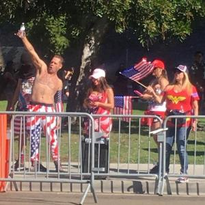 Five people dressed in American flag themed clothes, two holding American flags, standing on sidewalk behind metal barrier