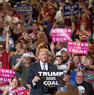 "Donald Trump at rally holding sign ""TRUMP DIGS COAL"""