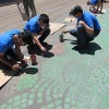 Three teens painting asphalt patio