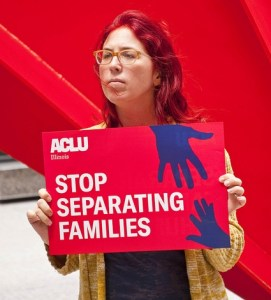 """Woman holding ACLU sign reading """"STOP SEPARATING FAMILIES"""""""