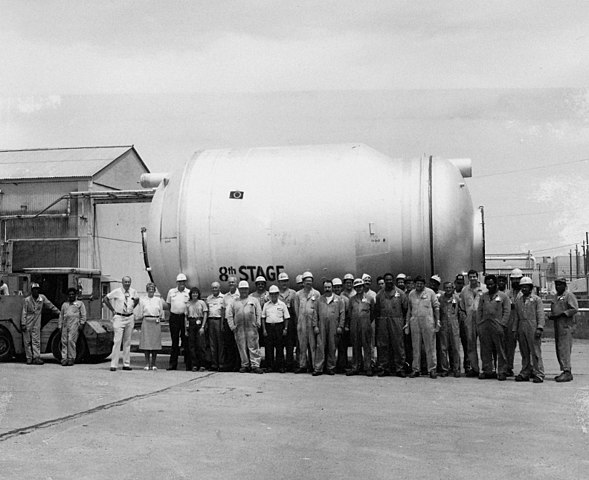"Group of workers standing in front of tank labeled ""8th STAGE"""