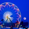 Night time view of Ferris Wheel with full moon in background