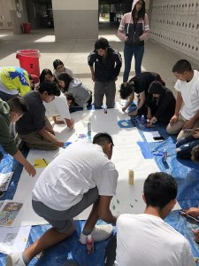 Group of teens gathered around a mural project laid out on the ground