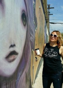 Woman standing next to wall mural