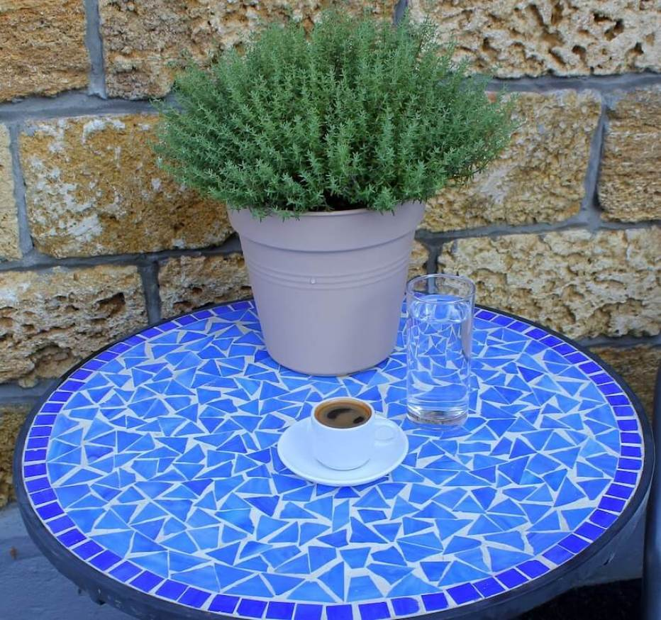 Greek coffee on a table with a rosemary plant