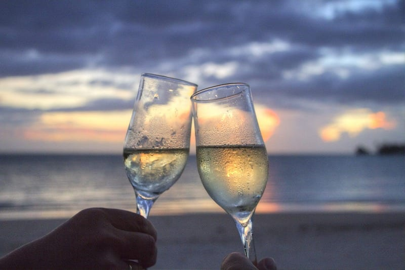 2 champagne glasses toasting. Dos and Don'ts in Malaysia