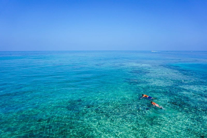 snorklers in clear blue water
