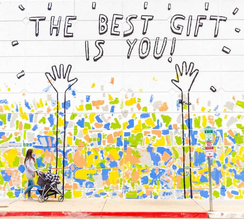 woman walking in front of mural that says the best gift is you