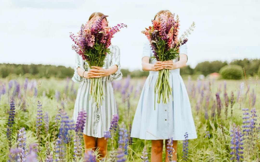 girls in fields with flowers covering their faces