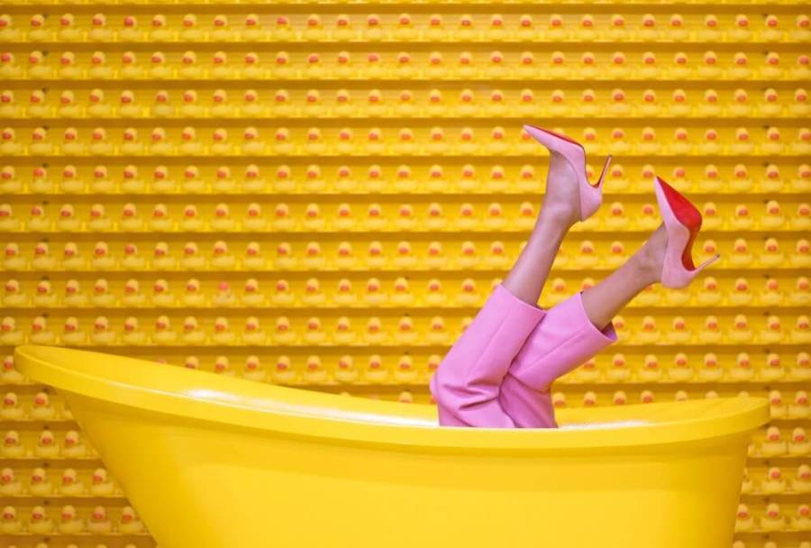 yellow background, legs in pink pants and heels popping out of tub.