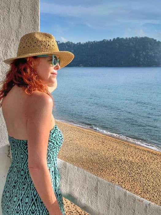 red head woman with hat looking out at ocean