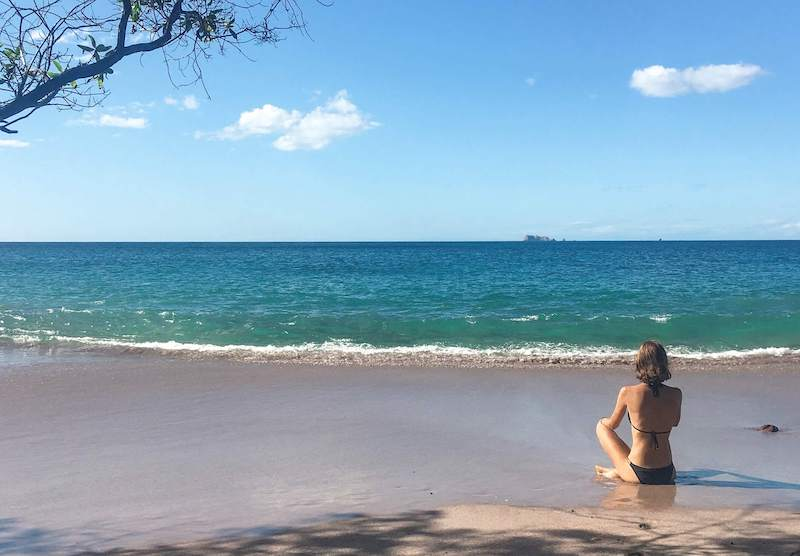 Emily sitting in the sand, staring at the ocean, on a Costa Rica beach. Reasons to move to another country