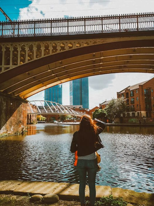 girl looking at river and Manchester bridge
