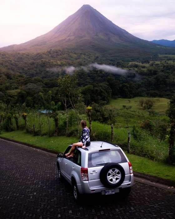 Girl sitting on car looking at Arenal Volcano, Costa Rica