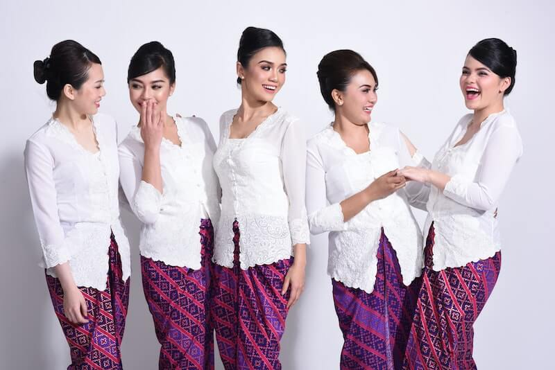 malaysian woman in white tops and batik skirts