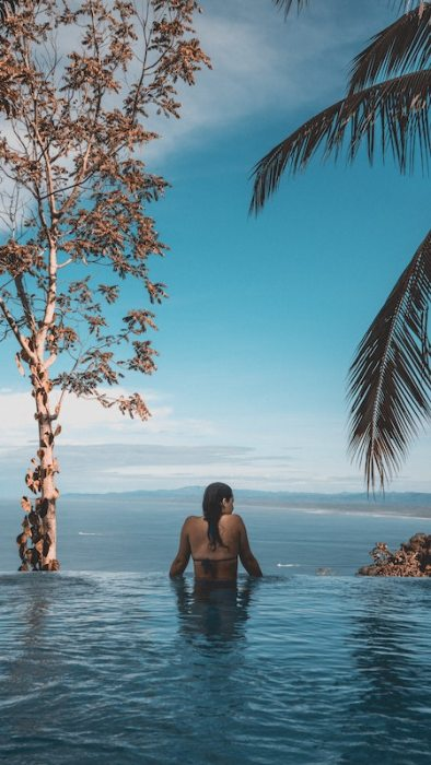 Woman in an infinity pool overlooking the ocean. You can have this if you live in Malaysia.