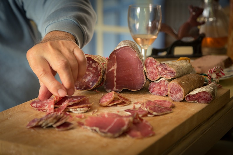 mans hand picking up salami with a glass of wine in the background