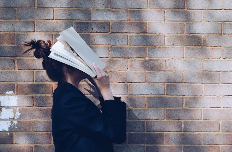 girl with book on face in front of brink wall