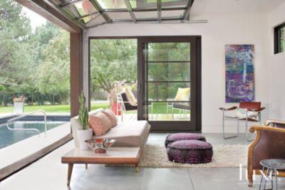 Modern pool house with garage door  Luxe Interiors  Design