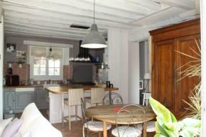 Cuisine ouverte avec îlot central, table ancienne, chaises bistrot, poutres peintes