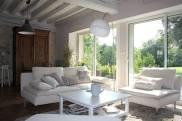 Salon ouvert sur le jardin, lumière naturelle, poutres grises, canapé et table basse clairs.