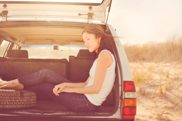 girl sitting in the back of an SUV
