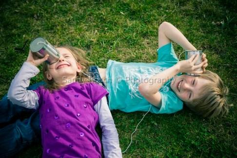 Junge und Mädchen spielen mit Büchsentelefon, Ergolding, Bayern, Deutschland