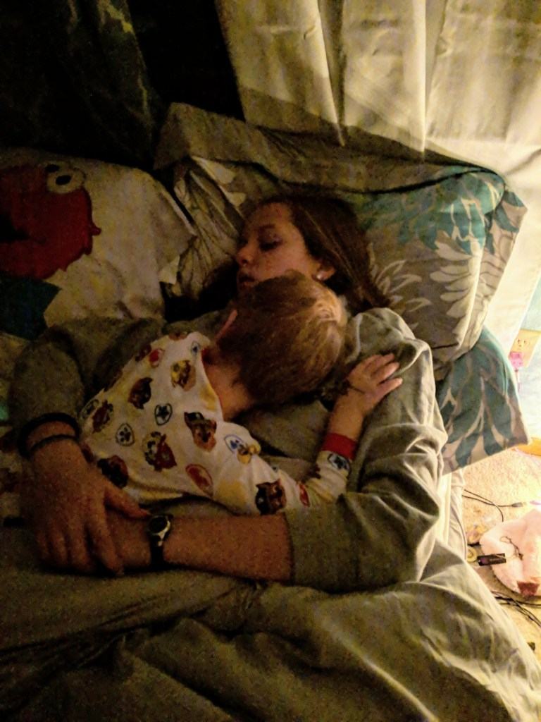 Brother and sister comforting each other at night