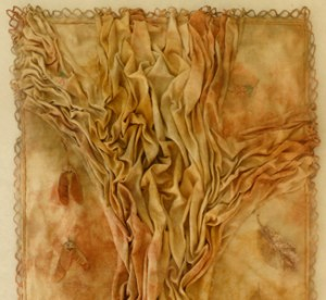 Lesley Turner, Forest Reliquary [top half], 2014 (28 x 16 in.), vintage tablecloth, earth dyes, leaf skeletons, deer bones, maple samaras, fern spores; earth dyeing, spore printing, hand stitching.
