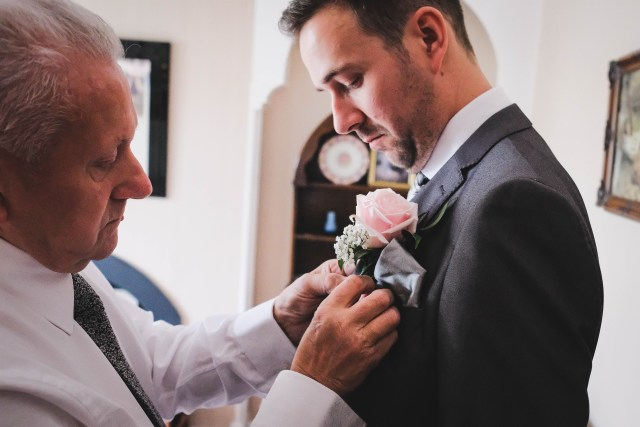 groom having buttonhole flower attached to suit