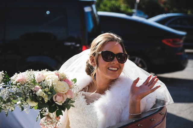 Bride in sunglasses arriving at church in a vintage convertible