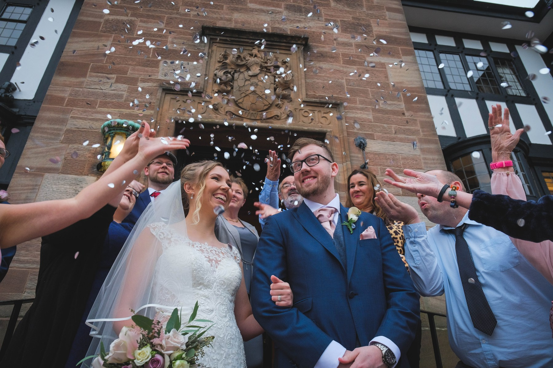 Bride and groom being showered with confetti at Inglewood Manor on the Wirral