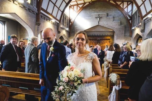 Bride and groom walk down the aisle at Saint Catherine's Church in Hoylake
