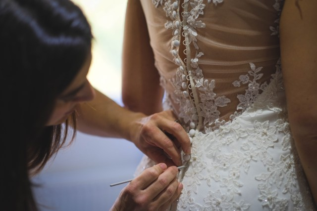 Fastening the buttons on the wedding dress