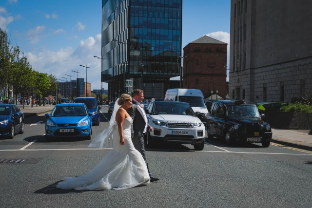 Bride and groom crossing The Strand for wedding photography in Liverpool