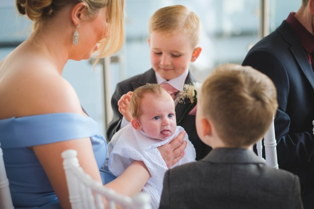 Baby sticking out tongue at wedding