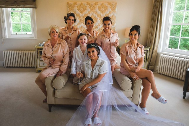 Bride and bridesmaids posing on bed for wedding photographer at Delamere Manor