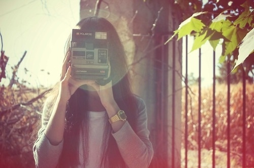 girl taking photo with polaroid