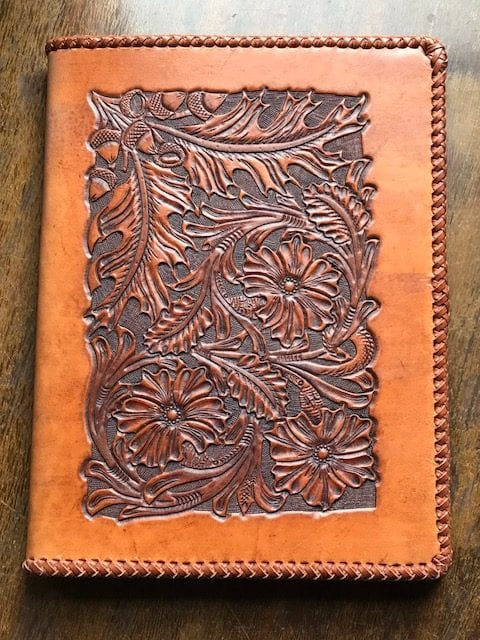 Notebook cover tooled in the Sheridan style of leather design. A Mexican round braid surrounds the edges of the notebook. The braid alone took 10 hours to complete and was done completely by hand.