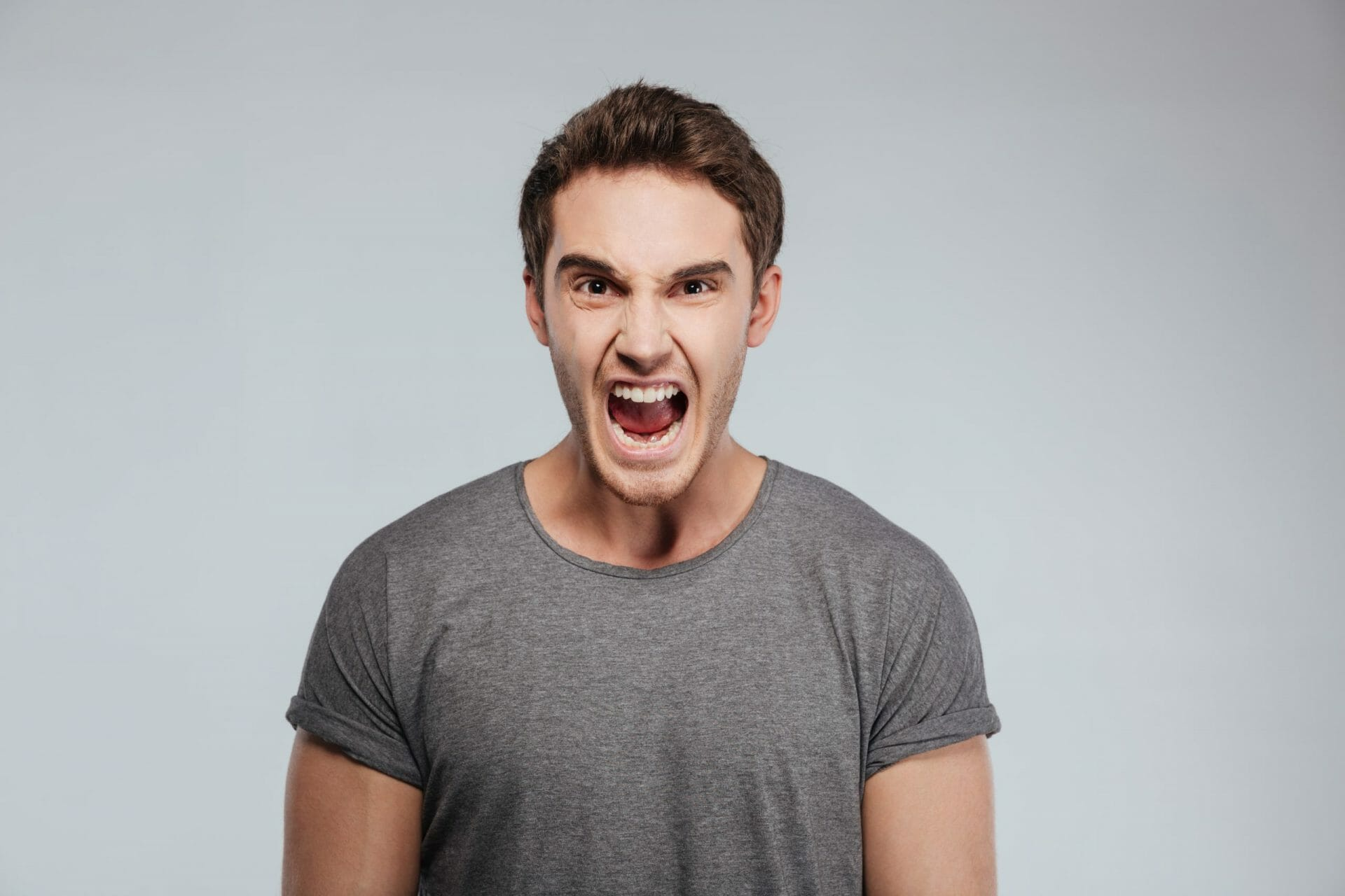 Portrait of a angry man screaming and looking at camera ...
