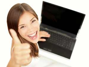 Happy woman with laptop thumbs up/saying yes/sanespaces.com