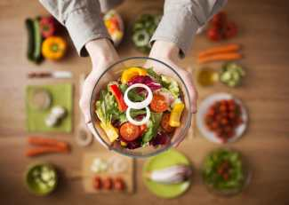 Hands holding a healthy fresh vegetarian salad in a bowl, fresh raw vegetables on background, top view