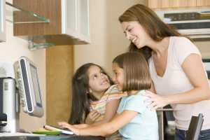 Studying Distractions, Woman and two young girls in kitchen with computer smiling