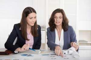 Two business woman analyzing balance sheet, customer trust