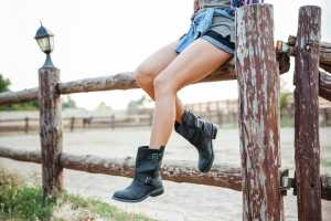 young woman boots sitting on fence