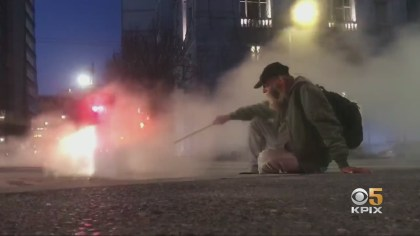 A homeless man huddles for warmth next to a steam vent near San Francisco City Hall. (CBS)