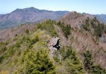 魅力の岩稜歩き、又岩場で休憩。後には御座山が大きい。
