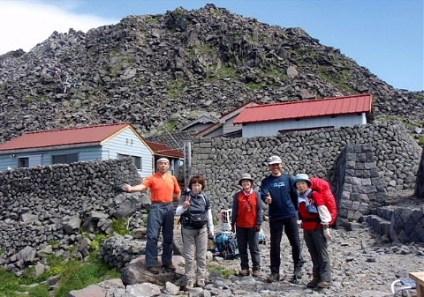 ⑤頂上御室にて新山2236m、大物忌神社をバックに。